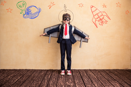 child education: Portrait of young businessman with toy paper wings. Success, creative and startup concept. Copy space for your text Stock Photo