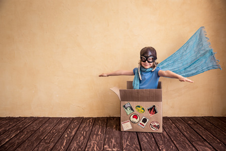 Happy child playing in cardboard box. Kid having fun at home