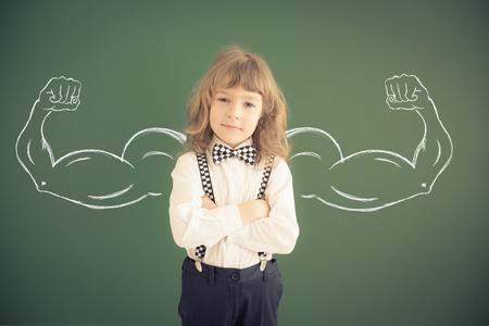 School jongen in de klas. Gelukkig kind tegen groene schoolbord. Onderwijs concept
