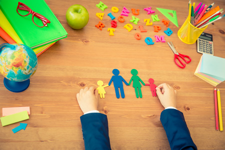 creative ideas: Child holding paper family in hands. School items on wooden desk in class. Education concept. Top view