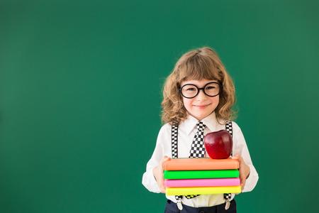Cabrito de la escuela en la clase. Niño feliz contra la pizarra verde. Concepto de la educación Foto de archivo - 43604607