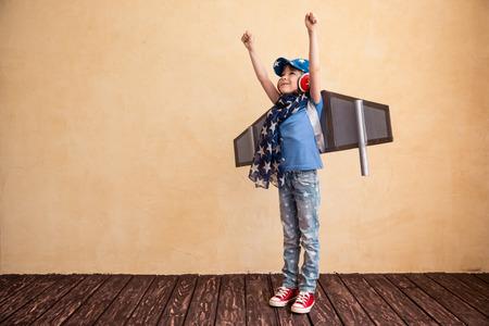 Gelukkig kind spelen thuis. Kid plezier met speelgoed papier vleugels Stockfoto