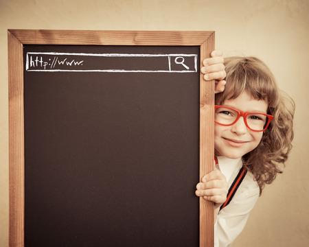 pizarron: Cabrito de la escuela en la clase. Niño feliz celebración de pizarra en blanco. Concepto de la educación