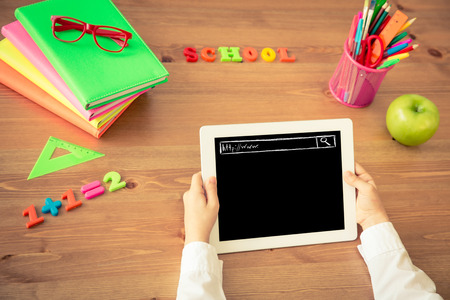 education: Child holding tablet PC in hands. School items on wooden desk in class. Education concept. Top view