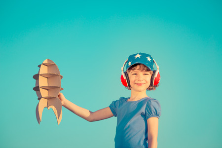 piloto: Ni�o feliz que juega con el cohete de juguete contra el cielo de verano de fondo