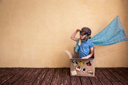 inspiracion: Niño feliz que juega en caja de cartón. Kid divertirse en casa