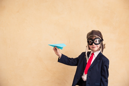 Portrait of young businessman with paper airplane. Success, creative and startup concept. Copy space for your text