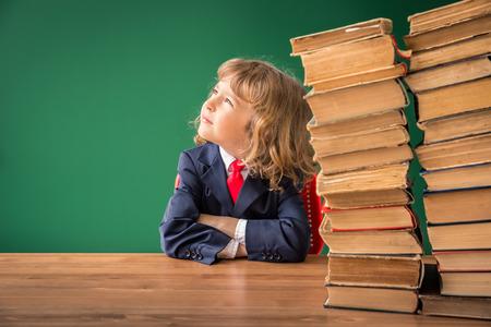 pizarron: Cabrito de la escuela en la clase. Niño feliz contra la pizarra verde. Concepto de la educación Foto de archivo