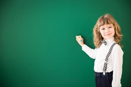 book concept: School kid in class. Happy child against green blackboard. Education concept