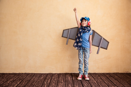 Happy child playing at home. Kid having fun with toy paper wings Stock Photo