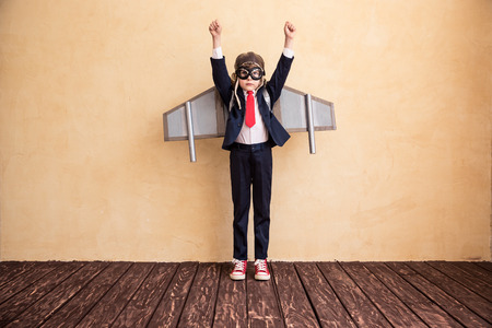 Portrait of young businessman with toy paper wings. Success, creative and startup concept. Copy space for your text 写真素材