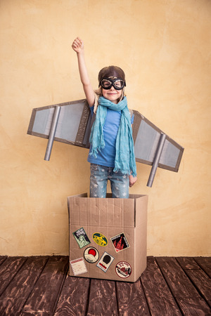 innovation concept: Happy child playing at home. Kid having fun with toy paper wings Stock Photo