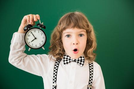 caras felices: Cabrito de la escuela en la clase. Niño feliz contra la pizarra verde. Concepto de la educación Foto de archivo