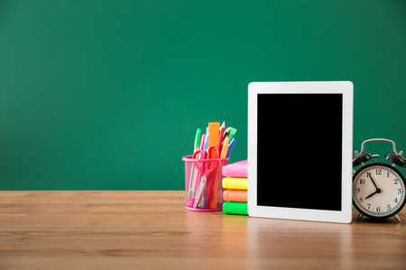 back to school background: Tablet PC in classroom against green blackboard. Education concept Stock Photo