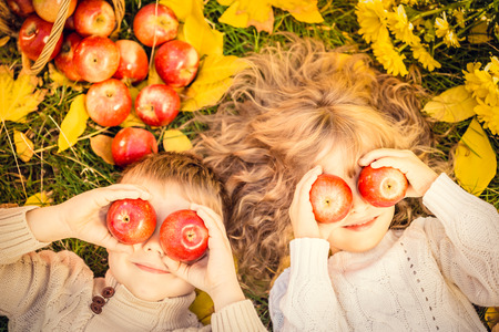 kinderschoenen: Gelukkige kinderen liggend op herfst bladeren. Grappige kinderen buiten in de herfst park