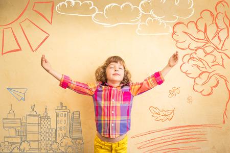 imaginacion: Niño feliz que juega en casa. Dibujo tema del otoño. La imaginación y el concepto de la libertad Foto de archivo
