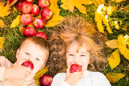 Autumn: Niños felices que mienten en hojas de otoño. Niños divertidos al aire libre en el Parque de otoño