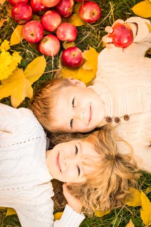 幸せな子供の上に横たわる秋葉。秋の公園で屋外面白い子供たち