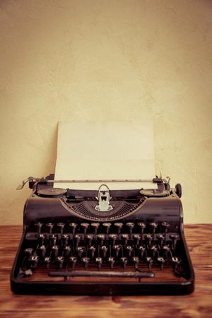 máquina de escribir: Máquina de escribir retra con el papel en blanco sobre la mesa de madera. Vista superior Foto de archivo