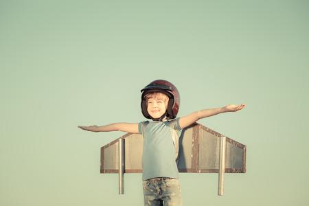 pilotos aviadores: Niño feliz que juega con las alas de juguete contra el fondo del cielo de verano. Retro tonificado