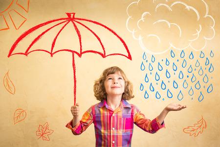 conceito: Criança feliz que joga em casa. Desenho tema do outono. Imaginação e liberdade conceito