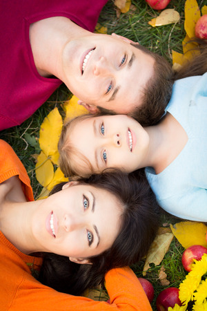 Happy family having fun outdoors in autumn park. Top view portrait Standard-Bild