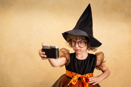 Lustiges Kind gekleidetes Hexenkostüm. Halloween Ferienkonzept