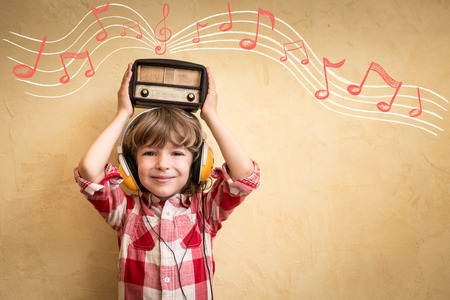 listen to music: Kid listen music at home. Hipster child with retro vintage radio Stock Photo