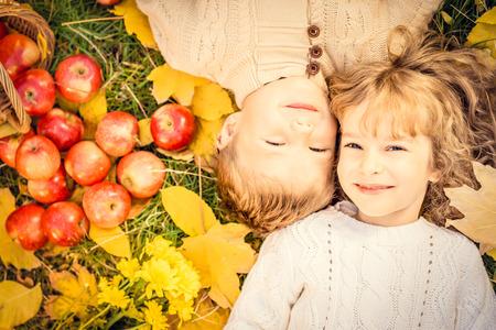 frutas divertidas: Niños felices que mienten en hojas de otoño. Niños divertidos al aire libre en el Parque de otoño