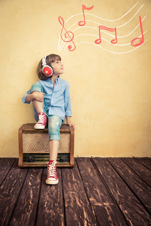Kid listen music at home. Hipster child with retro vintage radio Фото со стока