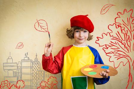 pintor: Ni�o feliz que juega en casa. Dibujo tema del oto�o. La imaginaci�n y el concepto de la libertad Foto de archivo