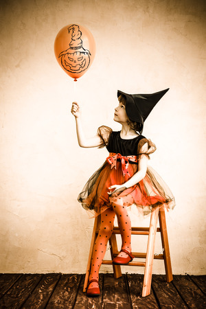 witch on broom: Funny child dressed witch costume. Halloween holidays concept