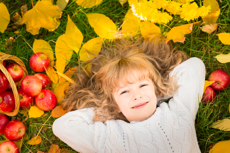 'leaf fall': Happy child lying on fall leaves. Funny kid outdoors in autumn park