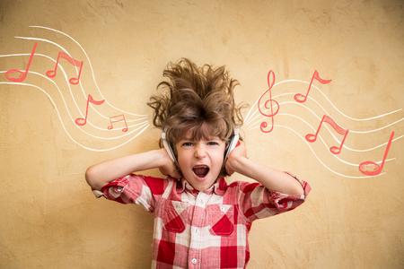 audifonos dj: Kid escuchar música en casa. Niño inconformista con auriculares. Concepto de la música Retro