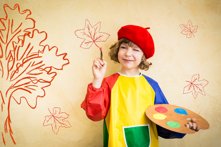 Happy child playing at home. Drawing autumn theme. Imagination and freedom concept