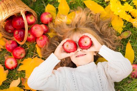 Gelukkig kind liggend op herfst bladeren. Grappig kind buiten in de herfst park