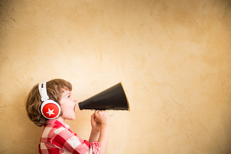 speaker: Kid listen music at home. Hipster child with retro vintage speaker