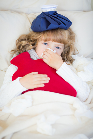 baby sick: Sick child with fever and hot water bottle at home Stock Photo