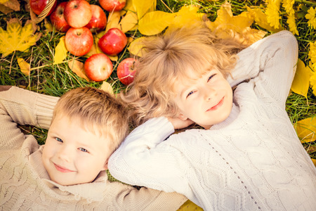 Happy children lying on fall leaves. Funny kids outdoors in autumn park