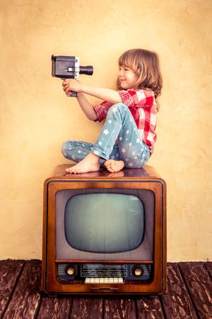 television antigua: Niño que juega en casa. Kid teniendo selfie con cámara retro. Concepto Cine