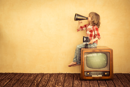 home video camera: Kid shouting through vintage megaphone. Communication concept. Retro TV