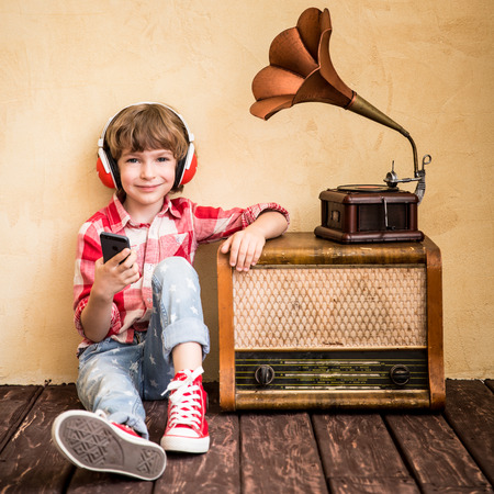 Kid listen music at home. Hipster child with retro vintage radio Stok Fotoğraf