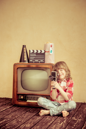 Child playing at home. Kid making a film with retro camera. Cinema concept Imagens - 45282206