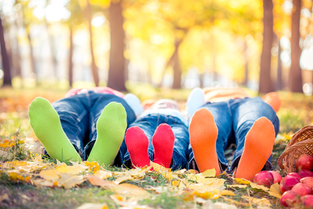 lying in leaves: Happy family having fun outdoors in autumn park