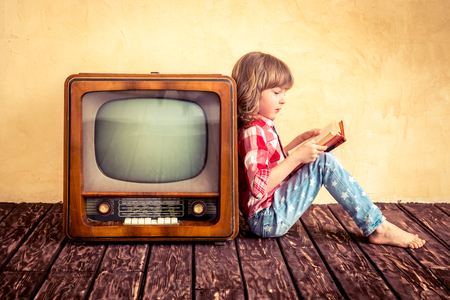 television: Child playing at home. Kid reading the book near retro TV. Cinema concept Stock Photo