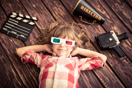 Child playing at home. Kid with vintage cinema objects. Entertainment concept. Top view 免版税图像