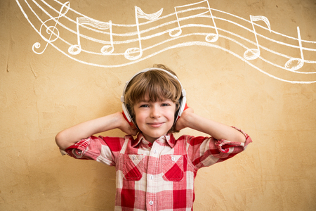 Kid listen music at home. Hipster child with headphones. Retro music concept