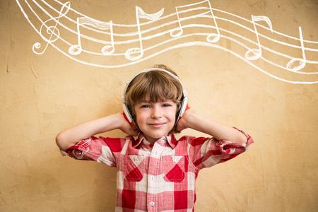 Kid luisteren muziek in huis. Hipster kind met een koptelefoon. Retro muziek concept