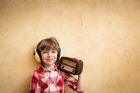 Kid luisteren muziek in huis. Hipster kind met retro vintage radio