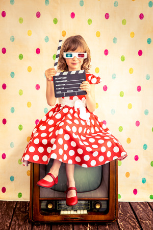 cinema film: Child playing at home. Girl holding clapper board. Cinema concept Stock Photo